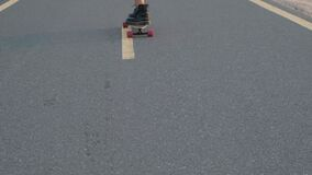 Girl rides on a skateboard on a desert road among the sand dunes. Close up.