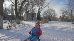 Girl rides a sled through the snow stock video footage
