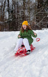 Girl rides sledge down hill. Girl slides down hill on red plastic sledge in a snowy winter park Stock Photography