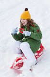Girl rides sledge down hill. Girl slides down hill on red plastic sledge in a snowy winter park Stock Image