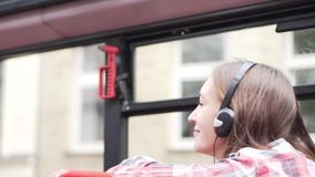 The girl rides in a tourist bus. And listens to the guide`s story about the city. Her headphones are on her head. She listens attentively and looks stock footage