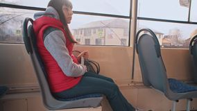 Girl rides the tram and listening to music. Young brunette woman in red sleeveless jacket listen to music on smartphone during tram ride.Girl looks out window stock video footage