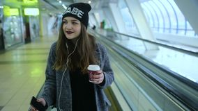 Girl rides on travelators and drink coffee stock video footage