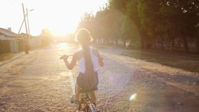 Girl is riding along road on bicycle in glare of setting sun. . Slow motion. Little girl is riding along road on bicycle in glare of setting sun. Slow motion stock video