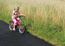 Girl riding the bicycle. Little girl riding the bicycle by the field stock photography