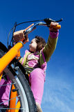 Girl riding a bicycle. A view from a young girl riding a bicycle under a bright blue sky royalty free stock images