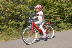 Girl riding bicycle Stock Photos