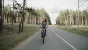 A girl is riding a bicycle on a country road. stock video