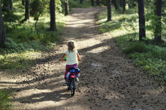 Girl riding a bicycle in the forest Royalty Free Stock Photos