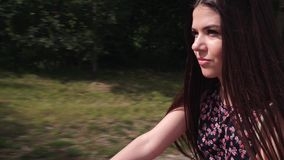 Girl riding a bicycle. Front view. Forest and clouds in the background stock footage