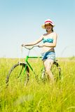 Girl riding bicycle in grass Royalty Free Stock Images