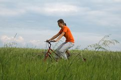 Girl riding bicycle in green field Royalty Free Stock Photography