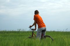 Girl riding bicycle in green field Royalty Free Stock Images