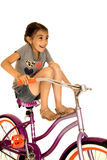 Girl riding bicycle with her legs up smiling funny photo Stock Photos