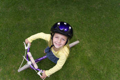 Girl riding bicycle on lawn royalty free stock photo