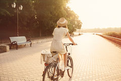 Girl riding a bicycle in park near the lake Stock Photography