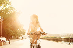 Girl riding a bicycle in park near the lake Stock Photos