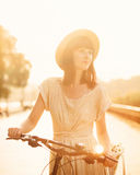 Girl riding a bicycle in park near the lake Royalty Free Stock Image