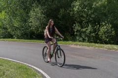 Girl riding a bicycle. Side view. Forest and clouds in the background Stock Images