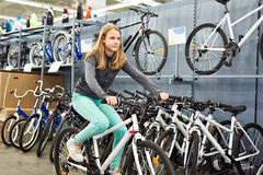Girl riding bicycle in sport shop Royalty Free Stock Photography