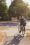 Girl Riding Bicycle into Sunset Stock Images