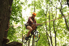 Girl riding bicycle on tightrope Stock Photo