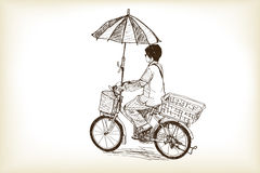 A girl riding bicycle to market and adapting umbrella on bicycl Royalty Free Stock Photos