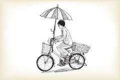 A girl riding bicycle to market and adapting umbrella  Royalty Free Stock Image