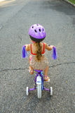 Girl Riding Bicycle with Training Wheels Royalty Free Stock Photos