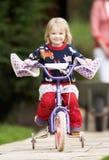 Girl Riding Bike Along Garden Path. Smiling To Camera Stock Image