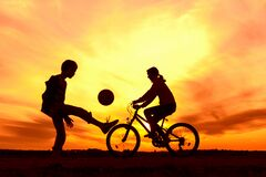 Girl riding bike in countryside, boy playing with ball outdoors