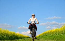 Girl riding a bike on a dirt road Stock Photography