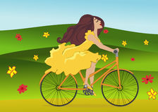 Girl is riding bike on flowering spring field Royalty Free Stock Image