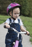 Girl riding a bike in a park Stock Photography