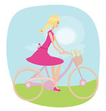 Girl is riding bike on spring field. Royalty Free Stock Photos