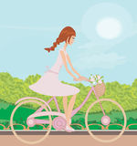 Girl is riding bike on spring field Stock Photos