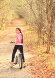 Girl riding a bike between trees Royalty Free Stock Photography