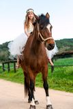 Girl riding brown horse. Stock Image