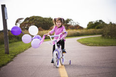 Girl riding a bycicle Royalty Free Stock Photos