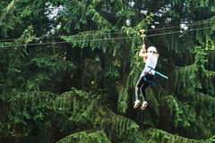 Girl riding cableway in forest adventure high wire park Stock Photography