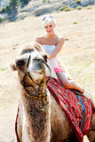 A girl riding a camel Stock Images