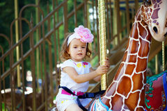 Girl riding on a carousel Royalty Free Stock Image