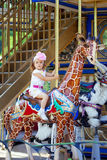 Girl riding on a carousel Royalty Free Stock Photography