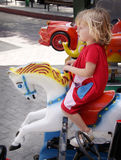 Girl riding a carousell horse. Girl at the merry-go-round, riding a play horse Royalty Free Stock Photos