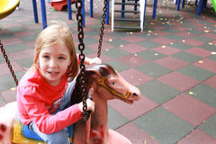 Girl riding a carousell horse Stock Images