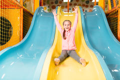 Girl riding from childrens slides on playground Stock Images