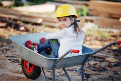 Girl riding in the construction wheelbarrow Stock Photos