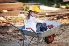 Girl riding in the construction wheelbarrow Stock Image