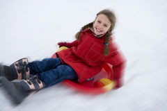 Girl (7-9) riding down snow on sled, smiling, portrait, elevated view (blurred motion) Royalty Free Stock Photography