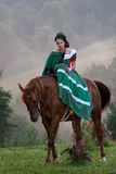 Girl riding equestrian classicism dress. In fog Stock Photography
